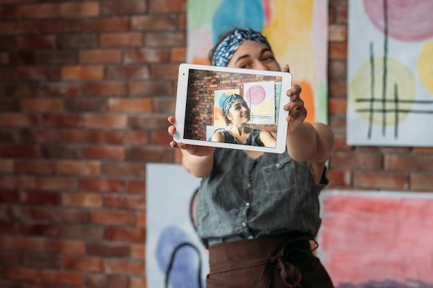 クリエイティブブロガー。彼女のアートワークで自分撮りをする才能のある女性アーティストuisngタブレット