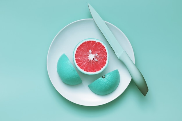 Creative blue grapefruit slices cut on plate with knife