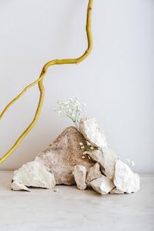 회색 벽에 천연 재료 돌 나무 꽃 식물 마른 가지와 창의적인 보헤미안 정물 구성. 돌로 만든 받침대. 추상 최소한의 흑백 베이지색 배경입니다.