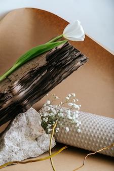 갈색 공예 종이에 천연 재료 돌 나무 종이 꽃 식물 마른 가지와 창조적 인 보헤미안 정물 구성. 추상 최소한의 흑백 베이지색 배경입니다.