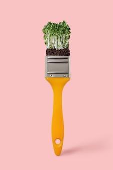 Креативная кисть с овощным свежим органическим микрозеленью на цветном фоне живого коралла 2019 года, место для текста. нетоксичная концептуальная живопись.
