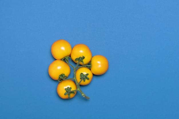 青の背景に黄色のトマトの創造的な束