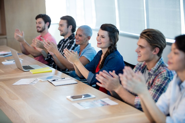 Creative business team applauding in meeting room at office