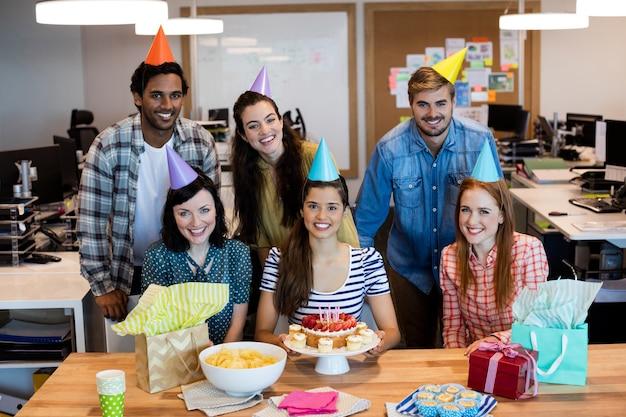 オフィスで同僚の誕生日を祝うクリエイティブなビジネスチーム