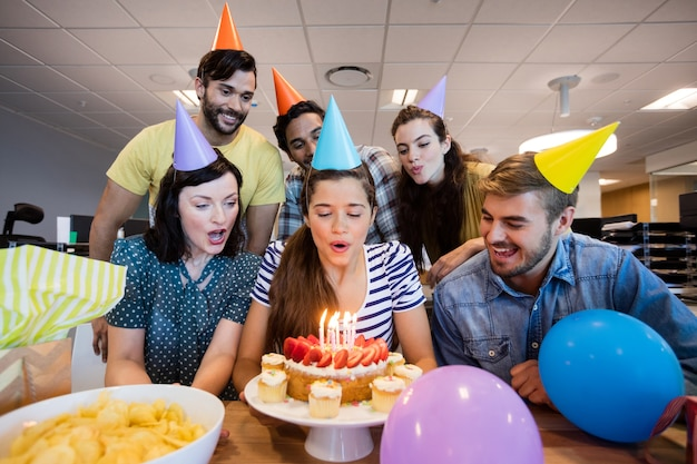 Creative business team celebrating colleagues birthday in office