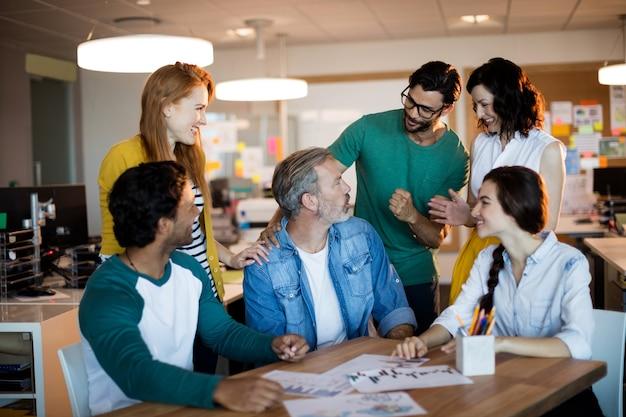 デスクのオフィスで話し合うクリエイティブなビジネスチーム
