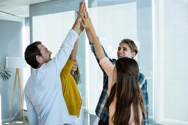オフィスでお互いにハイタッチをするクリエイティブビジネスチーム