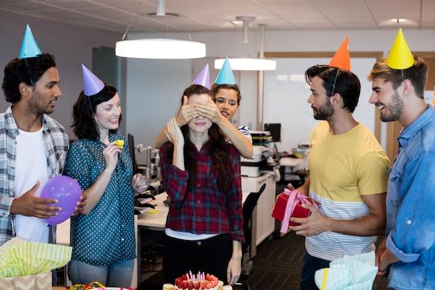 オフィスで彼女の誕生日に彼らの大学に驚きを与える創造的なビジネスチーム