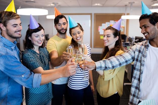 オフィスで同僚の誕生日に乾杯するクリエイティブなビジネスチーム