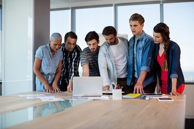 Творческая бизнес-команда, глядя на презентацию в ноутбуке в конференц-зале
