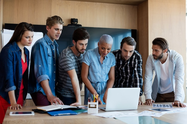 Creative business team looking at presentation in laptop at conference room