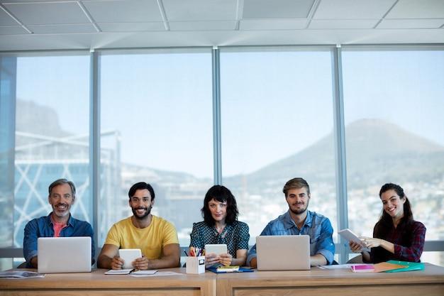 創造的なビジネスチームが並んで座って、オフィスのテーブルで一緒に働いています