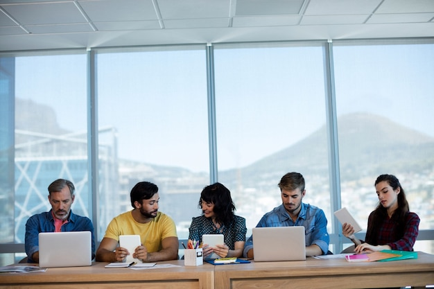 Creative business team sitting in a row and working together on table in office