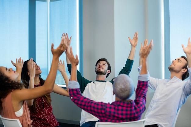 オフィスで腕を上げて座っている創造的なビジネスチーム