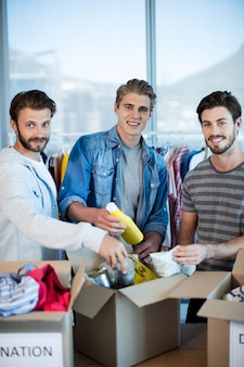 オフィスの募金箱で服を分類するクリエイティブビジネスチーム