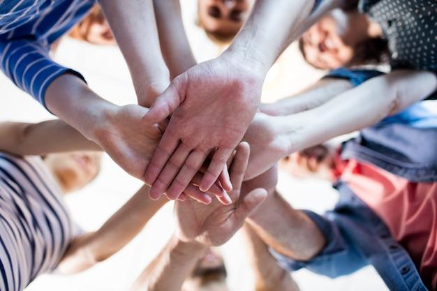 オフィスで手を積み重ねるクリエイティブなビジネスチーム