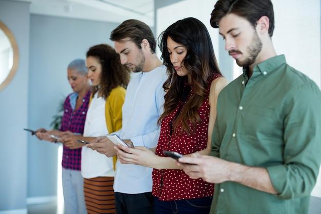 オフィスで携帯電話を使用するクリエイティブビジネスチーム