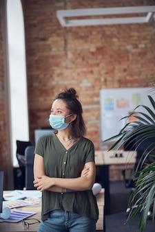 보호 마스크를 쓰고 옆을 바라보고 기대고 있는 평상복을 입은 창의적인 비즈니스 여성