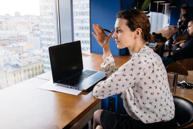 都市の景観と素敵な明るいオフィスでラップトップとスマートフォンに取り組んでいる創造的なビジネス女性