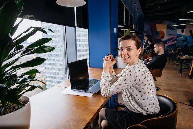 明るいモダンなオフィスでラップトップに取り組んでいる創造的なビジネス女性