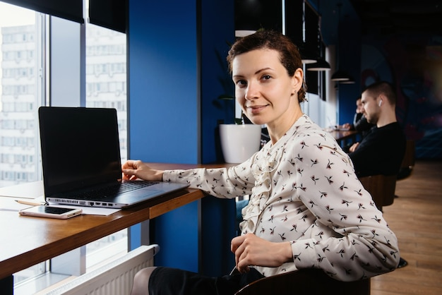 素敵な暗いオフィスでラップトップに取り組んでいる創造的なビジネス女性