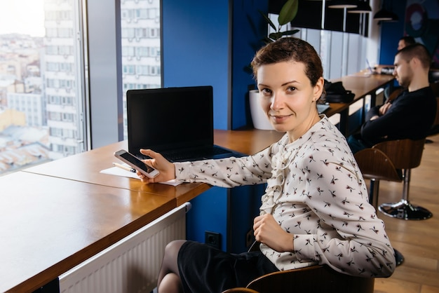 素敵な光のオフィスでラップトップに取り組んでいるクリエイティブなビジネスウーマン