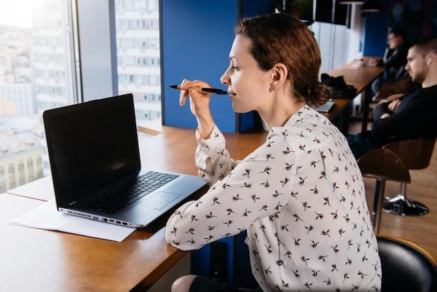 素敵なモダンなオフィスでラップトップに取り組んでいるクリエイティブなビジネスウーマン