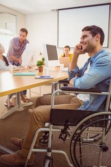 車椅子で創造的なビジネスマン電話