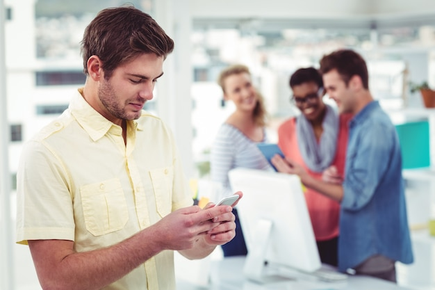 Creative businessman using smartphone in front of colleagues