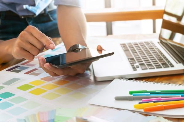 크리 에이 티브 사업가 태블릿을 사용하고 현대 사무실에서 책상에 컬러 차트 작업