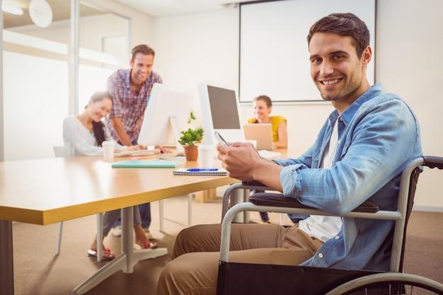 Creative businessman in wheelchair holding a phone