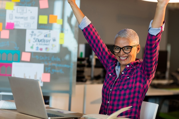 Creative businesswoman celebrating on desk at office
