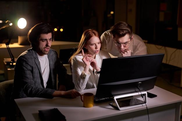밤에 회의실에서 일하는 창의적인 백인 사람들, 시작 사무실의 테이블에서 컴퓨터 작업을 하는 동료들은 마감일을 놓칩니다. 브레인스토밍, 비즈니스 프로젝트 개념