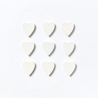 Креативный праздничный узор из бумажных сердечков ручной работы валентина на светло-серой стене с мягкими тенями, копией пространства.