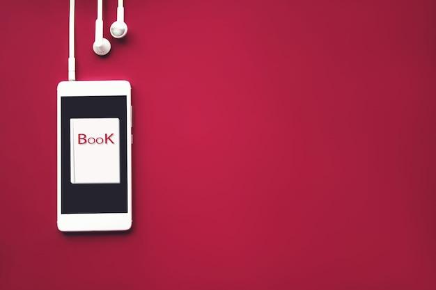 빨간색 배경에 헤드폰과 오디오북이 있는 창의적인 휴대폰. 오디오, 들어보세요. 오디오북 개념입니다.