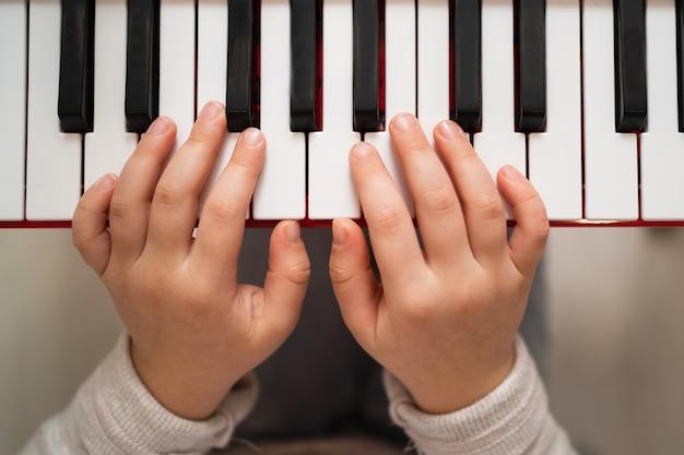 창의적인 아이가 신디사이저를 연주합니다. 피아노를 배우는 어린 소녀.