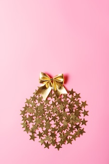 Creative christmas arrangement with golden stars in circle on pink background, conceptual design, copy space