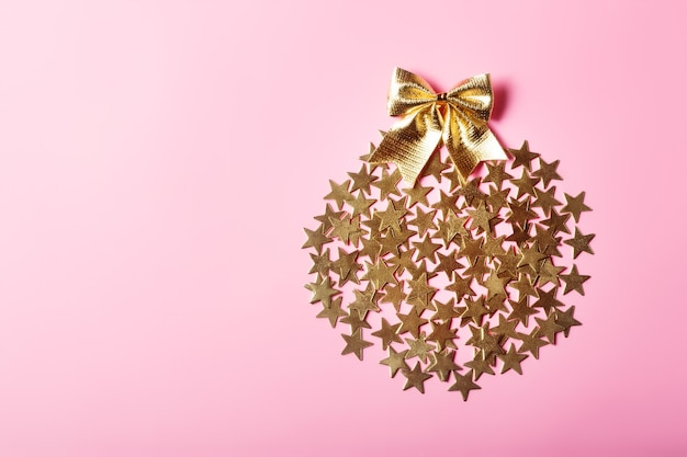 Creative christmas arrangement with golden stars in circle on pink background, glamour concept