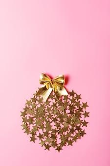 ピンクの背景、概念的なデザイン、コピースペースに円の黄金の星とクリエイティブなクリスマスのアレンジメント