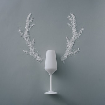 Creative christmas background with champagne flute and reindeer antlers formedof artificial winter snow on a silver rey background with copyspace