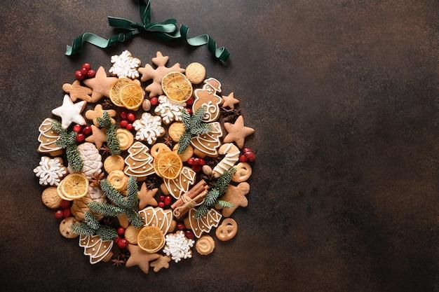 各種クッキー、シナモン、アニススター、ベリー、オレンジチップ、茶色の背景にトウヒの枝の創造的なクリスマスボール。新年のグリーティングカード。上面図。クリスマスの休日の背景。スペースをコピーします。