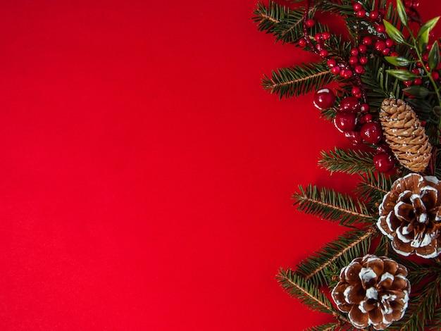 Креативная рождественская композиция из украшений и рождественской границы из еловой шишки на красной плоской планировке
