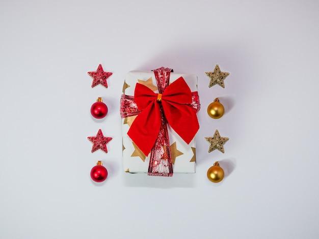 빨간 리본과 싸구려 크리스마스 장식 골드와 레드 플랫 선물 상자로 만든 크리 에이 티브 크리스마스 구성 평면도