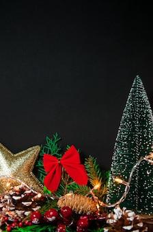 Креативная рождественская композиция с украшениями на темноте с вертикальным расположением рождественских огней, вид спереди