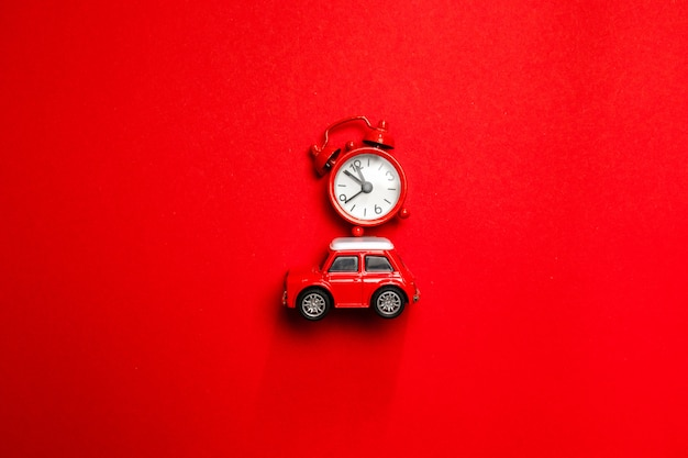 Creative christmas concept of red alarm clock round clock and toy car model on red background, top view. minimal creative holiday and travel concepts.
