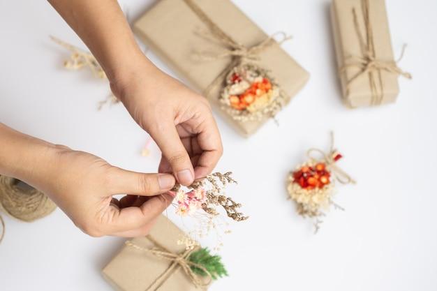 Творческое новогоднее ремесло хобби ручной работы. руки женщины украшая подарки с высушенным цветком.