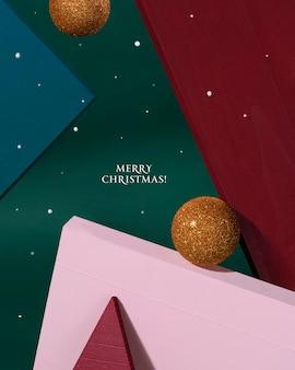 Творческий рождественский дизайн красный, зеленый, розовый цвет фона с золотой рождественской безделушкой и летающим снегом. новогодняя открытка. минималистичный стиль.