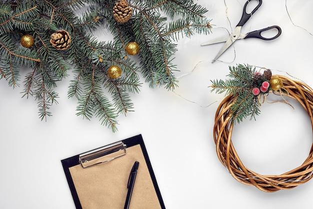 クリエイティブなクリスマスdiy。手作りのクリスマスリースを作る女性。ホームレジャー、ツール、装身具、白いテーブルの背景に休日の装飾の詳細。上面図