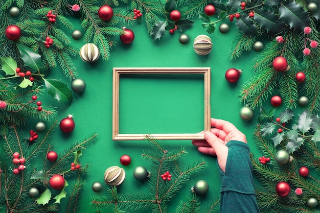 Creative christmas flat lay on green paper with copy-space. female hand holding empty frame. decorative border made of fir and holly twigs, green and red trinkets, dry lime fruit and frosted berries.