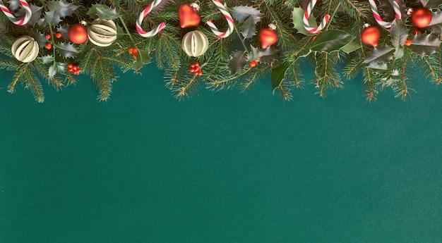 創造的なクリスマスフラットはコピースペースをたっぷりと赤い装飾と緑の紙の上に置いた。キャンディー、ガラスの小物、ライムのドライフルーツで飾られた自然のモミとヒイラギの小枝。